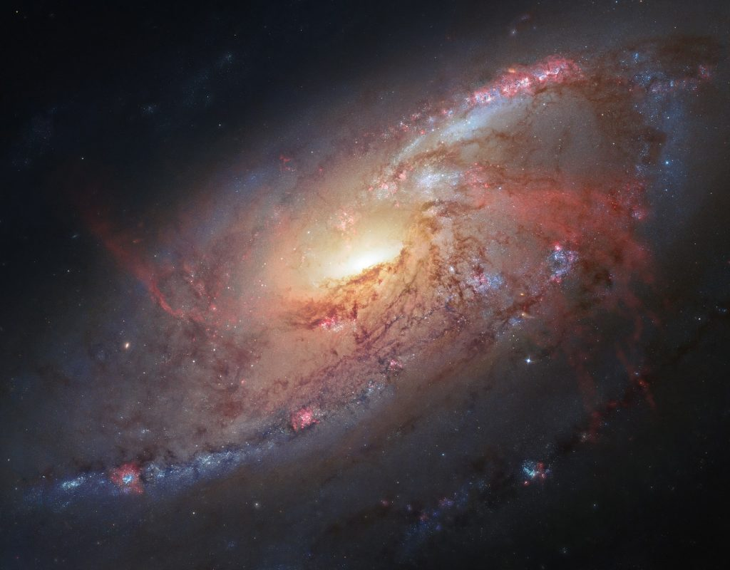This image combines Hubble observations of M 106 with additional information captured by amateur astronomers Robert Gendler and Jay GaBany. Gendler combined Hubble data with his own observations to produce this stunning colour image. M 106 is a relatively nearby spiral galaxy, a little over 20 million light-years away.